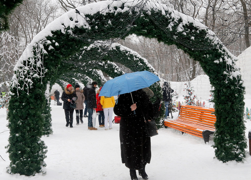 . A woman covers herself with a blue umbrella as it snows in a city park in Kiev, Ukraine, Tuesday, Jan. 10, 2017. The temperature in Kiev is -6 degrees Centigrade (22 degrees Fahrenheit). (AP Photos/Efrem Lukatsky)