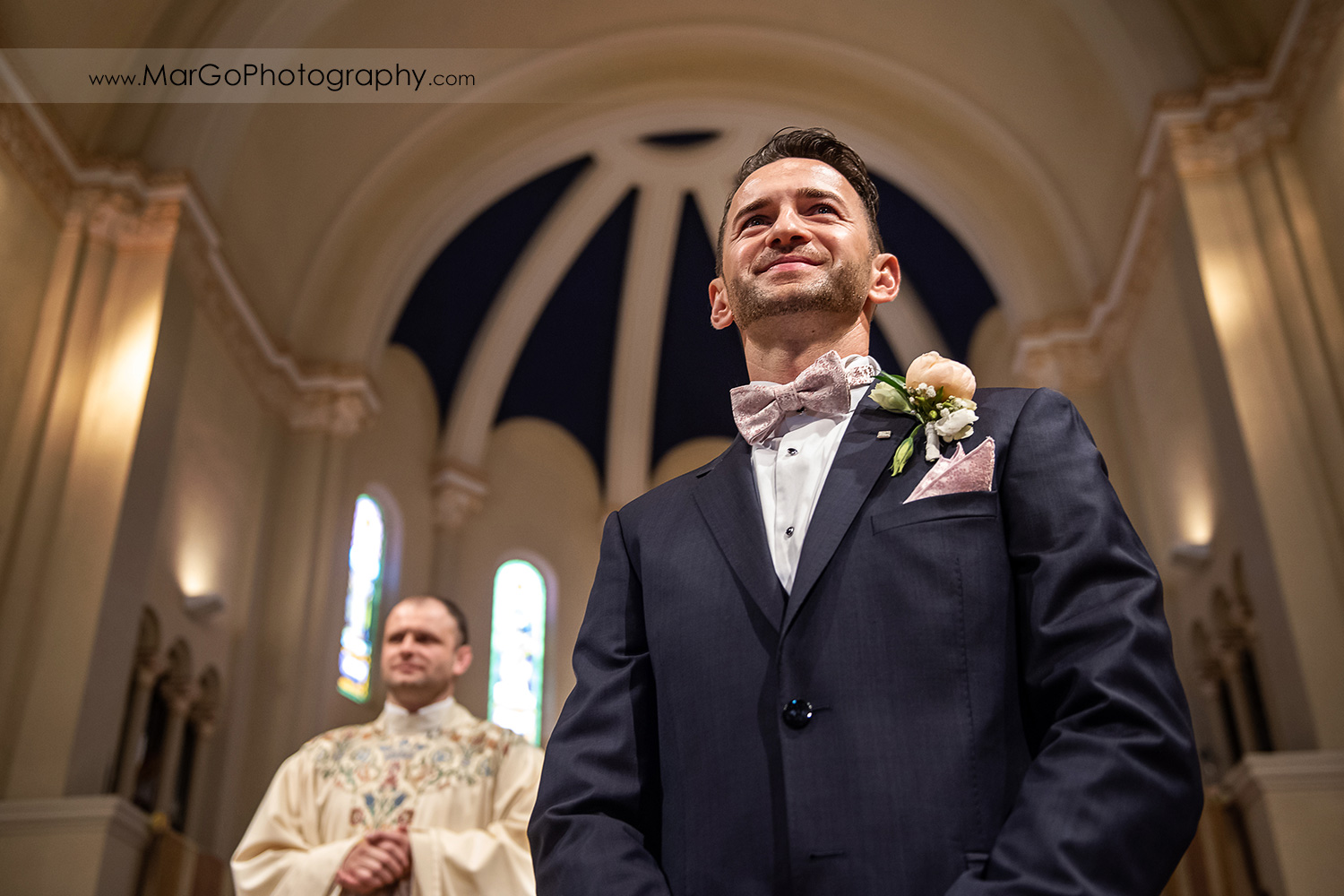 groom waiting for bride walking down the aisle during wedding ceremony at Oakland Church of Saint Leo the Great