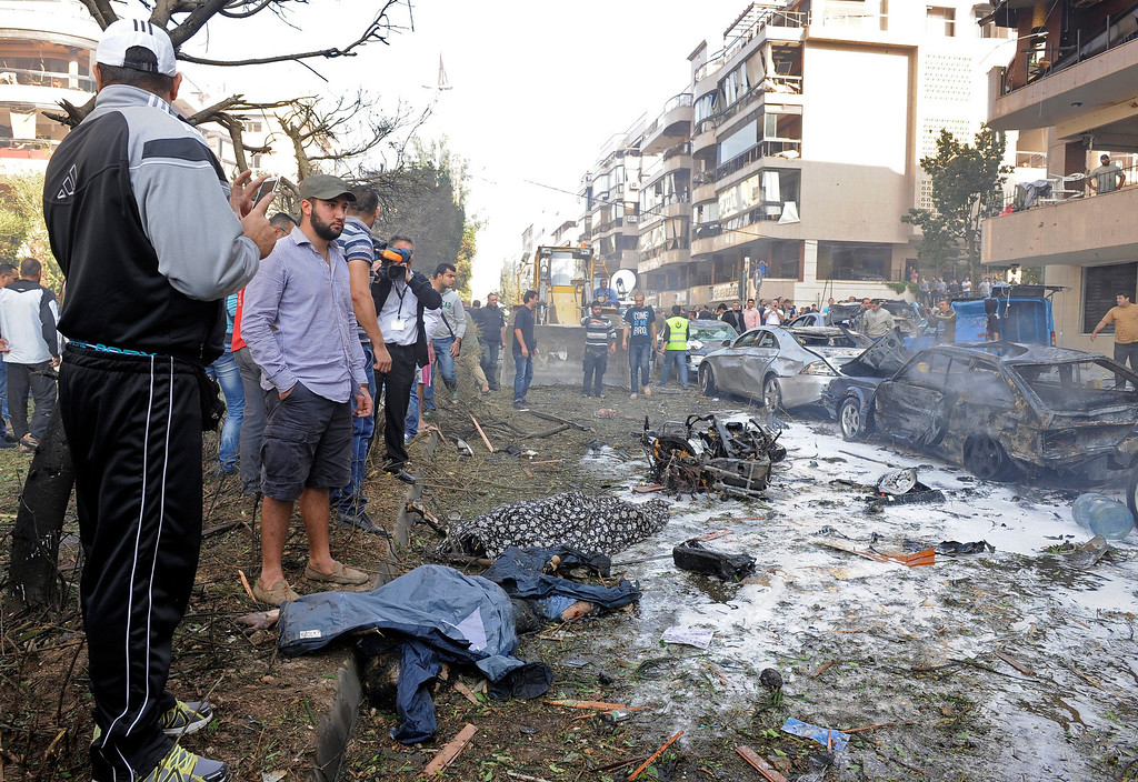 . Two men stands over a dead bodies at the scene after a number of explosions near the Iranian embassy in Beirut, Lebanon, 19 November 2013. The death toll from a double suicide bombing near the Iranian embassy in Beirut has risen to 23, including at least two Iranian citizens, the Lebanese Health Ministry says and about 146 others were wounded.  EPA/WAEL HAMZEH