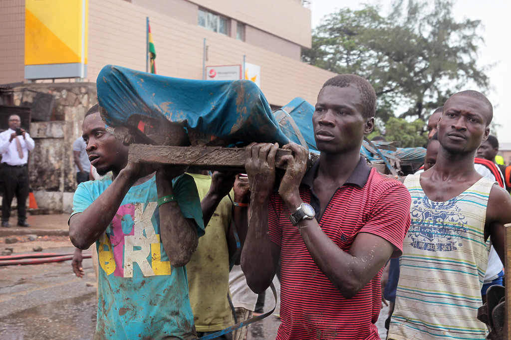 . Rescue workers carry the remains, of a person a killed in a gas station explosion in Accra, Ghana, Thursday, June 4, 2015. Flooding in Ghana\'s capital swept stored fuel into a nearby fire, setting off a huge explosion at a gas station that killed scores of people and set alight neighboring buildings, authorities said Thursday. (AP Photo/Christian Thompson)