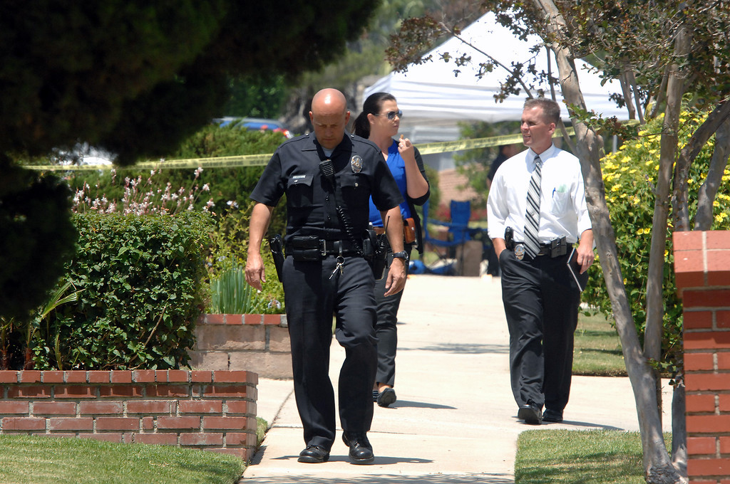 . LAPD personnel walk the scene on the 19200 block of Kenya Street in Northridge, Friday, June 15, 2013, where a woman was murdered and the suspect surrendered to SWAT officers following a nighttime standoff. (Michael Owen Baker/Staff Photographer)