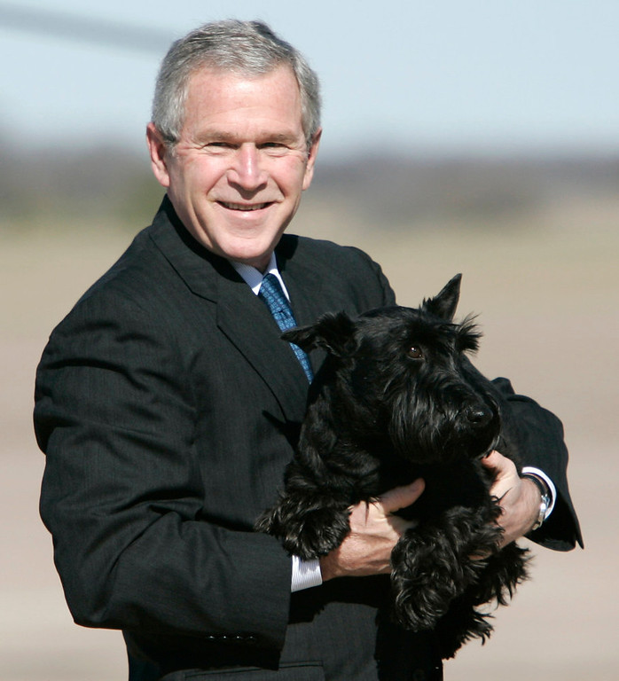 . In this Dec. 26, 2006 file photo, President George W. Bush carries his dog Barney across the airport tarmac in Waco, Texas.  (AP Photo/Evan Vucci, File)