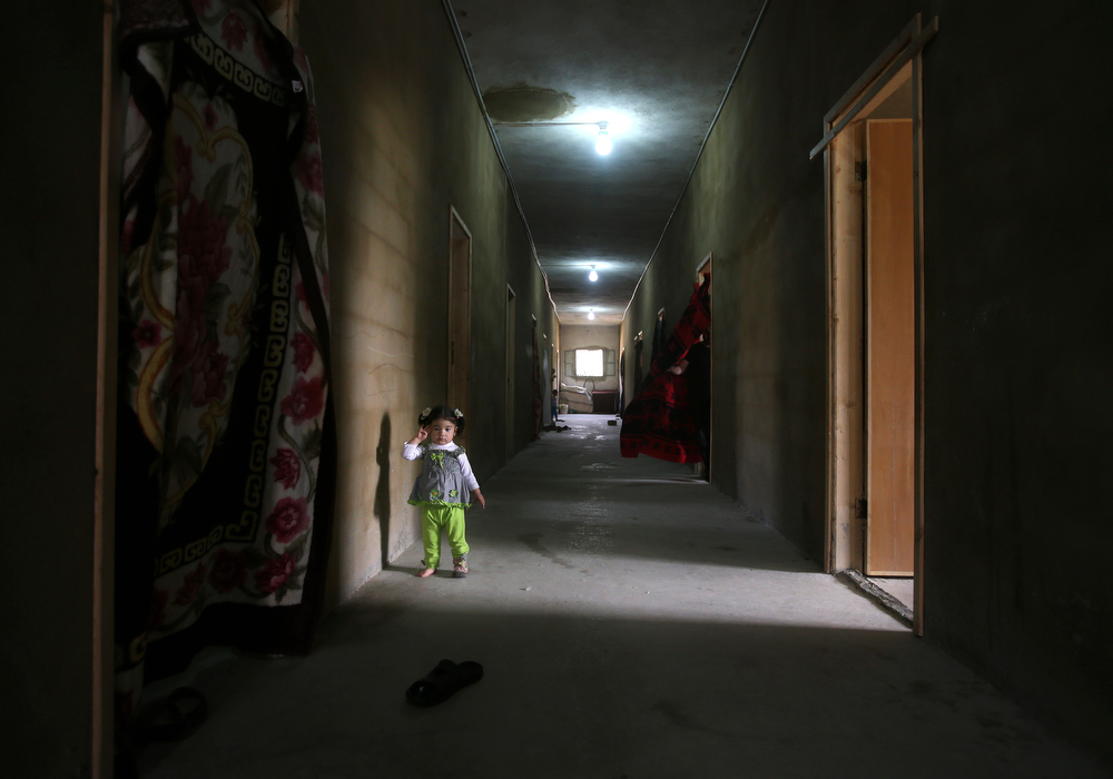 . In this picture taken on Thursday, May 29, 2014, a Syrian refugee girl stands in the corridor of a collective center where she lives with her family, in Kirbet Daoud village in Akkar, north Lebanon. (AP Photo/Hussein Malla)