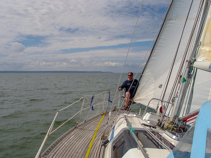 Brian sitting in the bows of SYCORAX during a passage sail to Ouistreham
