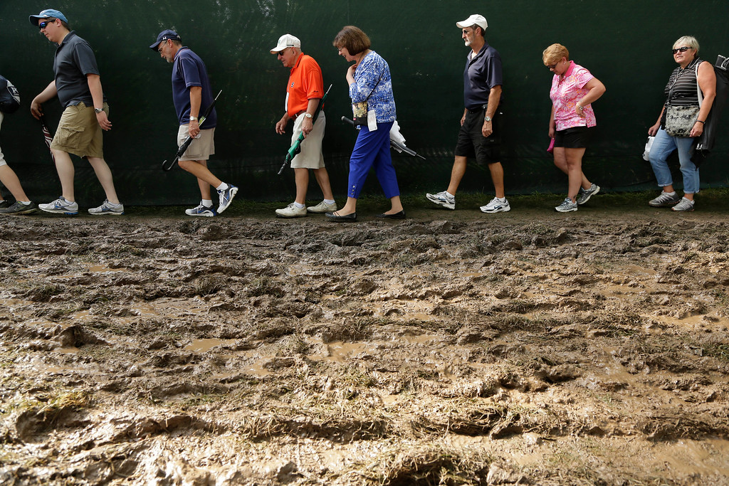 . Golf fans bypass mud created by an early rain storm during the second round of the PGA Championship golf tournament at Oak Hill Country Club, Friday, Aug. 9, 2013, in Pittsford, N.Y. (AP Photo/Charlie Riedel)