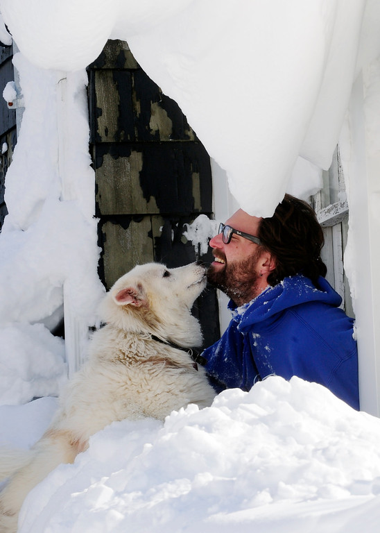 . Steve Corbett opens his window under snow drifts and greets his neighbor\'s dog Wednesday, Nov. 19, 2014, on Central Ave in Lancaster, N.Y. A lake-effect snow storm dumped over five feet of snow in areas across Western New York. Another two to three feet of snow is expected s expected in the area, bringing snow totals to over 100 inches, almost a years\' worth of snow in three days.  (AP photo/Gary Wiepert)