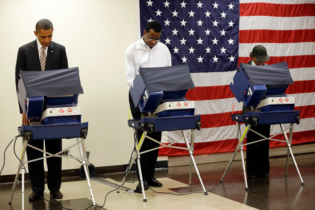 . President Barack Obama, left, casts his vote during early voting in the 2012 election Thursday, Oct. 25, 2012, in Chicago, at the Martin Luther King Community Center. (AP Photo/Pablo Martinez Monsivais)