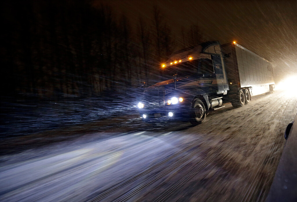 . A tractor trailer rig drives during a snowstorm along the Atlantic City Expressway,  Friday, Jan. 22, 2016, near Atlantic City. Most of the state was facing a blizzard warning from Friday evening until Sunday that called for up to 24 inches of snow, with the deepest accumulations in the central part of the state. (AP Photo/Mel Evans)