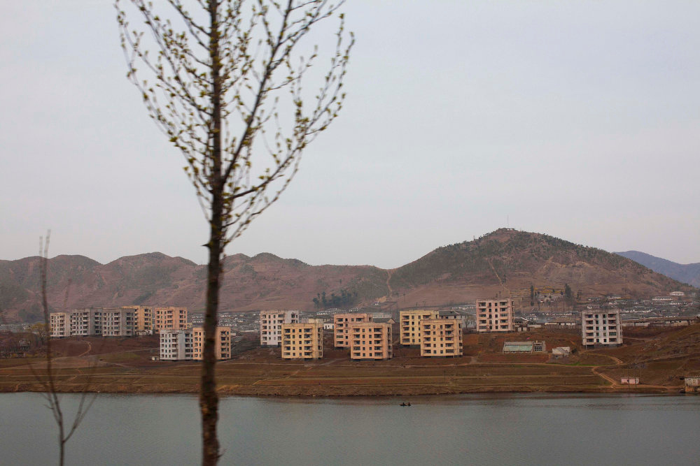 Description of . Buildings sit next to a small body of water in a North Korean town along the highway from Pyongyang to the southern city of Kaesong on April 17, 2011.  (AP Photo/David Guttenfelder)