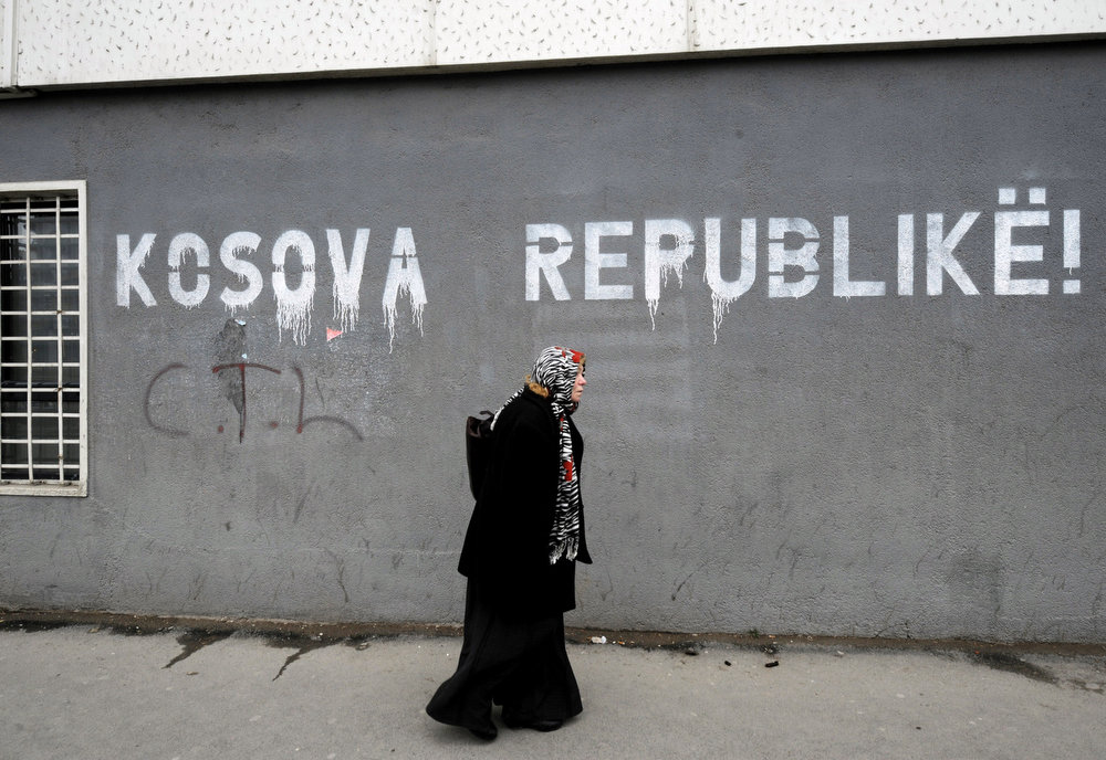 Description of . A Kosovo Albanian woman walks past graffiti reading