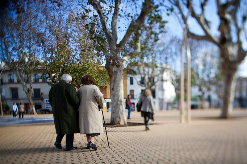 Elderly couple walking, Alameda de Hercules square, Seville, Spain. Tilted lens used for shallower depth of field.