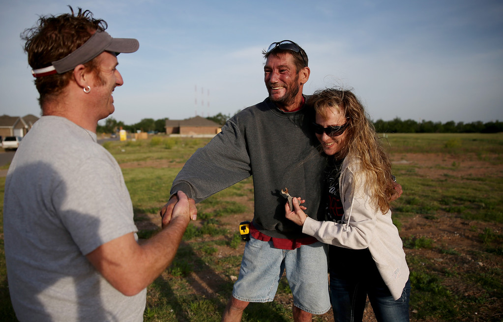 . Rodney Cartmill (C) greets David Friess and his wife Ann Friess as they return to remember their pets on the spot where their house once stood and the pets died one year ago when a tornado passed through the area on May 20, 2014 in Moore, Oklahoma.  On May 20, 2013 a two-mile wide EF5 tornado touched down in the town killing 24 people and leaving behind extensive damage to homes and businesses.  (Photo by Joe Raedle/Getty Images)