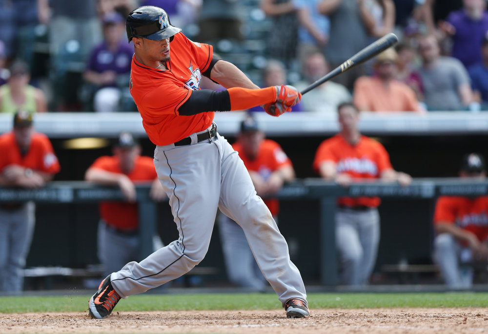 . Miami Marlins\' Giancarlo Stanton strikes out while swinging at a pitch against the Colorado Rockies to end the ninth inning of the Rockies\' 7-4 victory in a baseball game in Denver on Sunday, Aug. 24, 2014. (AP Photo/David Zalubowski)