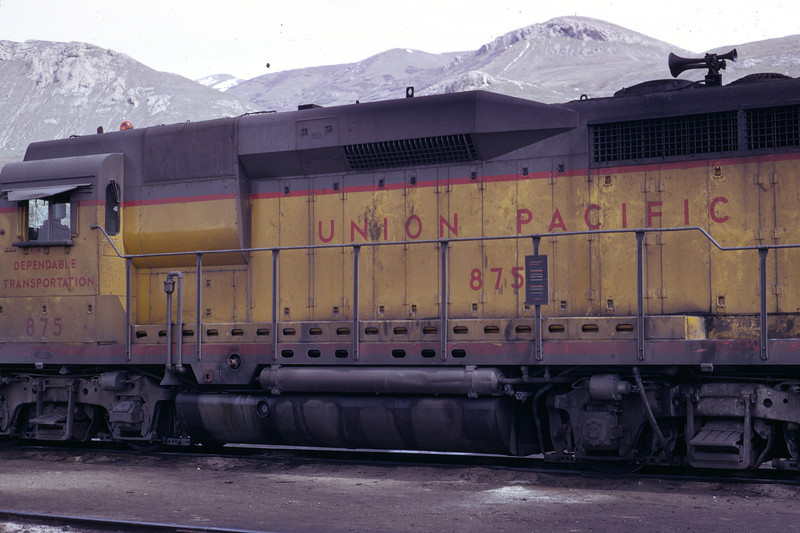 A view of the left side of UP 875, the former EMD GP30 demonstrator. Note the shortened traction motor blower enclosure, immediately behind the cab. Later EMD units had their blower enclosures here, including GP30s, but since the blower duct crossed to the opposite side of the unit on GP30s, the enclosure is short on this unit, but extended to the walkway on all other GP30s. Salt Lake City, April 1973. (Don Strack Photo)