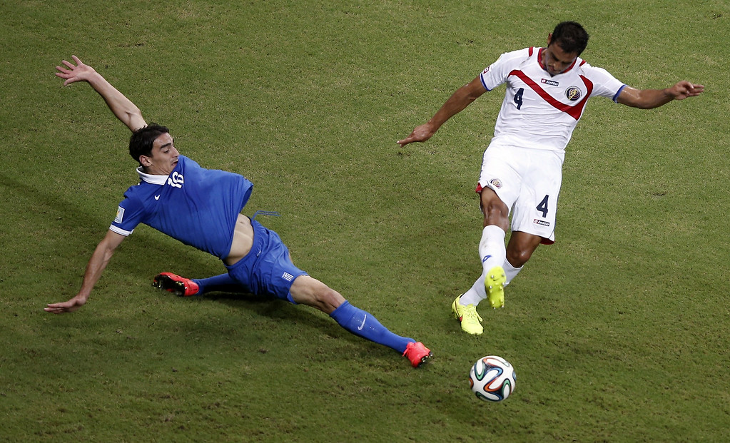. Costa Rica\'s defender Michael Umana (R) challenges Greece\'s midfielder Lazaros Christodoulopoulos during the round of 16 football match between Costa Rica and Greece at Pernambuco Arena in Recife during the 2014 FIFA World Cup on June 29, 2014.   ADRIAN DENNIS/AFP/Getty Images
