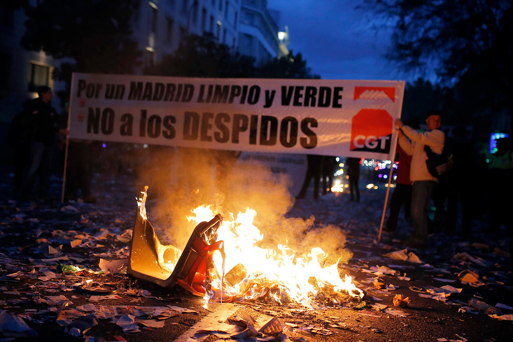 """. Protestors burn trash as they carry a banner reading \""""Madrid clean and green. No layoffs!\"""" during a demonstration against layoffs of street cleaners and garbage collectors in Madrid, Spain, Monday, Nov. 4, 2013. Trash collectors in Madrid have started bonfires and set off firecrackers during a noisy protest in one of the Spanish capitalís main squares as they prepare to start an open-ended strike. (AP Photo/Andres Kudacki)"""