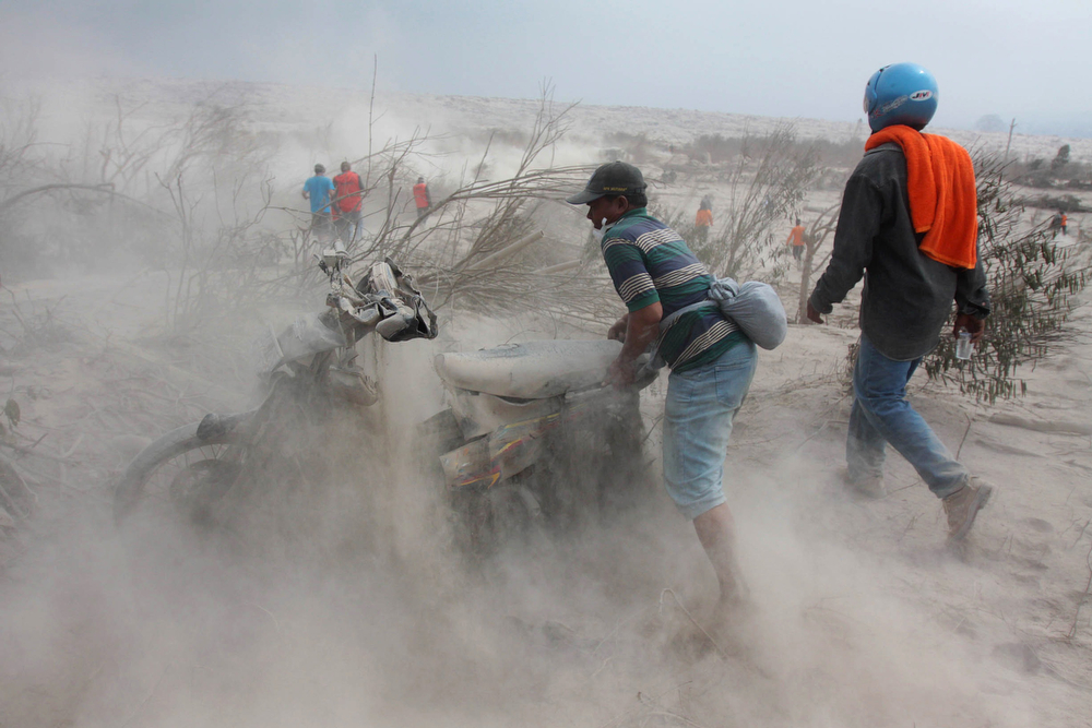 . Indonesian rescuers lift an abandoned motorcycle in the ash-covered two-kilometre danger zone from the crater of Mount Sinabung volcano in Karo district on February 2, 2014 as teams look for more victims of the eruption. Indonesian officials searched through thick ash for bodies after Mount Sinabung volcano erupted, killing at least 15 people, with the only sign of life an ownerless mobile phone ringing inside an abandoned bag. (ATAR/AFP/Getty Images)