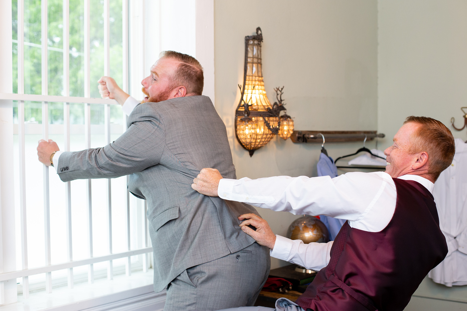 groom jokingly trying to crawl out of a window on his wedding day as one of his groomsmen is pulling him back in