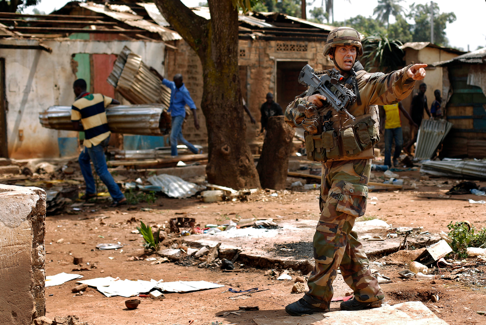 . French forces push looters out, in the Miskin district in Bangui, Central African Republic, Monday Feb. 3, 2014. Fighting between Muslim Seleka militias and Christian anti-Balaka factions continues as French and African Union forces struggle to contain the bloodshed. (AP Photo/Jerome Delay)