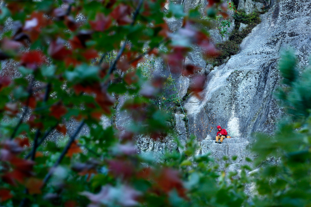 . High above the fall foliage, a rock climber takes a break from belaying his partner to use his phone halfway up Cathedral Ledge, a 500-foot cliff, Thursday, Sept. 28, 2017, in North Conway, N.H. (AP Photo/Robert F. Bukaty)
