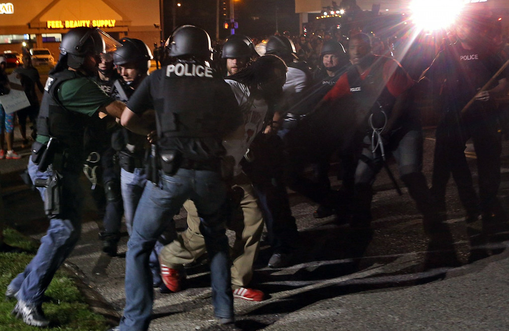 . Police detain a protester Monday, Aug. 18, 2014, in Ferguson, Mo. The Aug. 9 shooting of Michael Brown by police has touched off rancorous protests in Ferguson, a St. Louis suburb where police have used riot gear and tear gas. (AP Photo/St. Louis Post-Dispatch, J.B. Forbes)