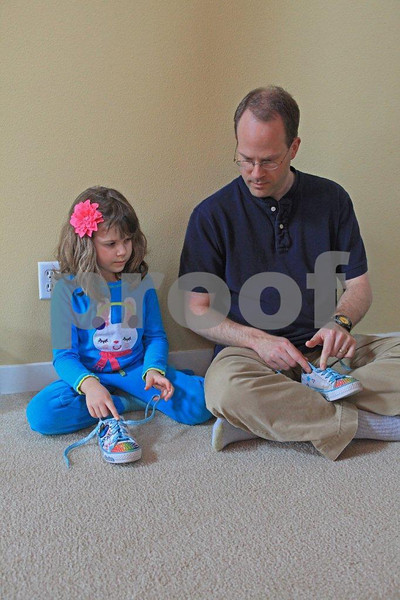 Father teaches his five-year old daughter how to tie her shoes.