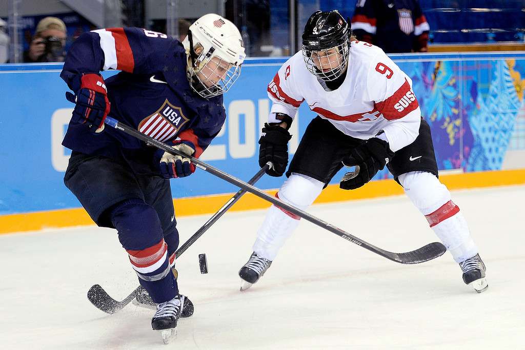 . Kendall Coyne (26) of the U.S.A. controls the puck as Stefanie Marty (9) of the Switzerland defends during the second period of action at the Shayba Arena. Sochi 2014 Winter Olympics on Monday, February 10, 2014. (Photo by AAron Ontiveroz/The Denver Post)