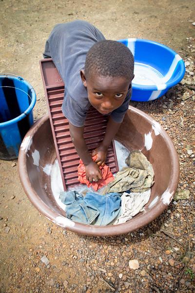 Monrovia, Liberia October 8, 2017 -  A young boy washes clothes.