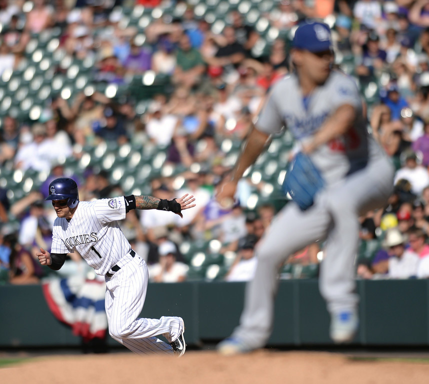 . DENVER, CO - JULY 5:  Colorado baserunner Brandon Barnes took off for second base with Dodgers reliever Brandon League on the mound. The Colorado Rockies defeated the Los Angeles Dodgers 8-7 at Coors Field Saturday afternoon, July 5, 2014.  Photo by Karl Gehring/The Denver Post