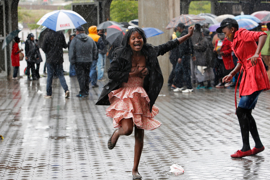 . Two girls dance in the rain outside of the  the memorial service for former South African president Nelson Mandela at the FNB Stadium in Soweto, near Johannesburg, South Africa, Tuesday Dec. 10, 2013. (AP Photo/Tsvangirayi Mukwazhi)