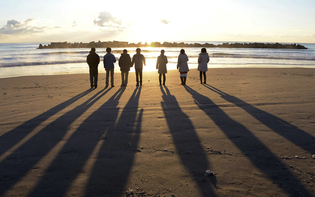 . A group members sing a gospel song along seaside in Sendai, Miyagi, northern Japan as the sun rises over the area devastated by March 11, 2011 earthquake and tsunami, on Tuesday, Jan. 1, 2013. (AP Photo/Kyodo News)