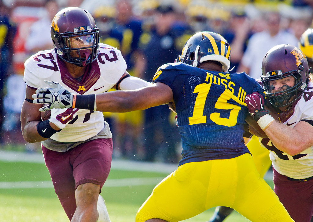 . Minnesota running back David Cobb (27) gets an assist to avoid Michigan linebacker James Ross III (15) from teammate Miles Thomas, right, in the second quarter of an NCAA college football game in Ann Arbor, Mich., Saturday, Sept. 27, 2014. (AP Photo/Tony Ding)