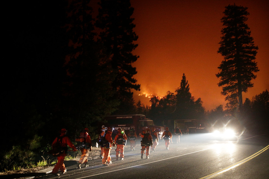. Firefighters walk toward their trucks as the Rim Fire continues to burn near Yosemite National Park, Calif., on Saturday, Aug. 24, 2013. Fire crews are clearing brush and setting sprinklers to protect two groves of giant sequoias as a massive week-old wildfire rages along the remote northwest edge of Yosemite National Park. (AP Photo/Jae C. Hong)