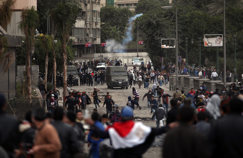 . Egyptian protesters clash with riot police near Tahrir Square, Cairo, Egypt, Monday, Jan. 28, 2013. Health and security officials say a protester has been killed in clashes between rock-throwing demonstrators and police near Tahrir Square in central Cairo. The officials say the protester died Monday on the way to the hospital after being shot. (AP Photo/Khalil Hamra)