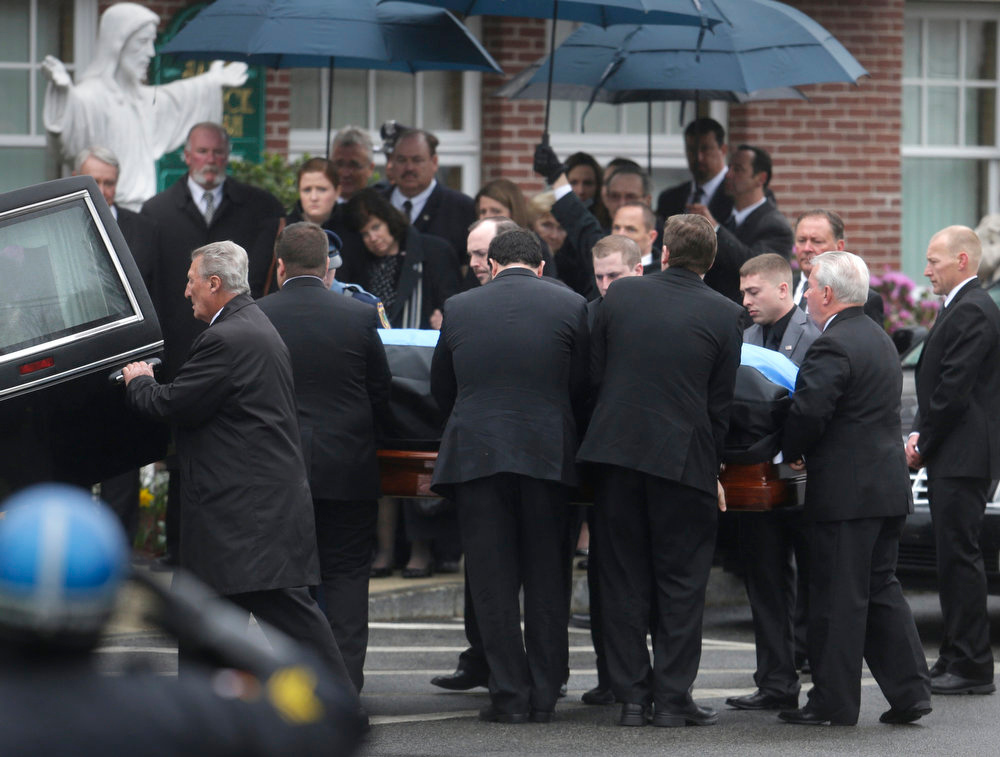 . Pallbearers carry the casket of fallen Massachusetts Institute of Technology police officer Sean Collier into St. Patrick\'s Church before a funeral Mass, in Stoneham, Mass., Tuesday, April 23, 2013. Collier was fatally shot on the MIT campus Thursday, April 18, 2013. Authorities allege that the Boston Marathon bombing suspects were responsible. (AP Photo/Steven Senne)