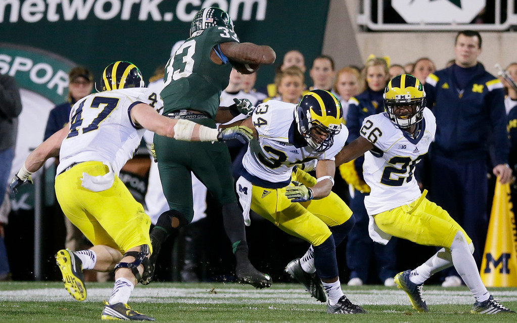 . Michigan State running back Jeremy Langford (33) breaks through the defense of Michigan linebacker Jake Ryan (47), and defensive backs Jeremy Clark (34) and Jourdan Lewis (26) for a 5-yard touchdown during the second half of an NCAA college football game in East Lansing, Mich., Saturday, Oct. 25, 2014. (AP Photo/Carlos Osorio)