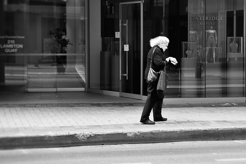 A woman waiting for a bus to arrive in downtown Wellington checks the time on her watch.