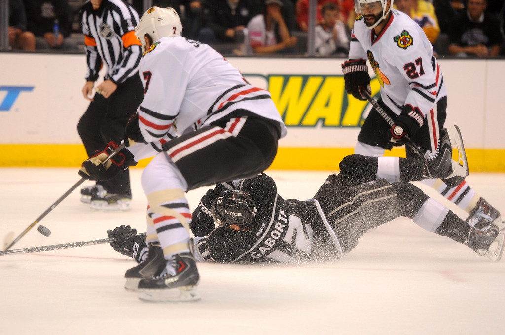 . The Kings\' Marian Gaborik hits the ice as he is defended by the Blackhawks\' Brent Seabrook, left, and Johnny Oduya during game six of the Western Conference Finals, Friday, May 30, 2014, at Staples Center. (Photo by Michael Owen Baker/Los Angeles Daily News)