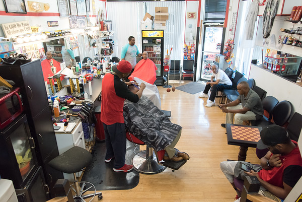 05/24/18 Wesley Bunnell | Staff Jimmie &quote;Sauce&quote; Spencer, L, and Johnny Turner , L rear, work on their clients hair at Blaze Barber Shop on Thursday afternoon as customers sit in the waiting area. The barbershop is a place of discussion everyday including topics as the NFL's recent decision to require on field personnel to stand for the National Anthem.