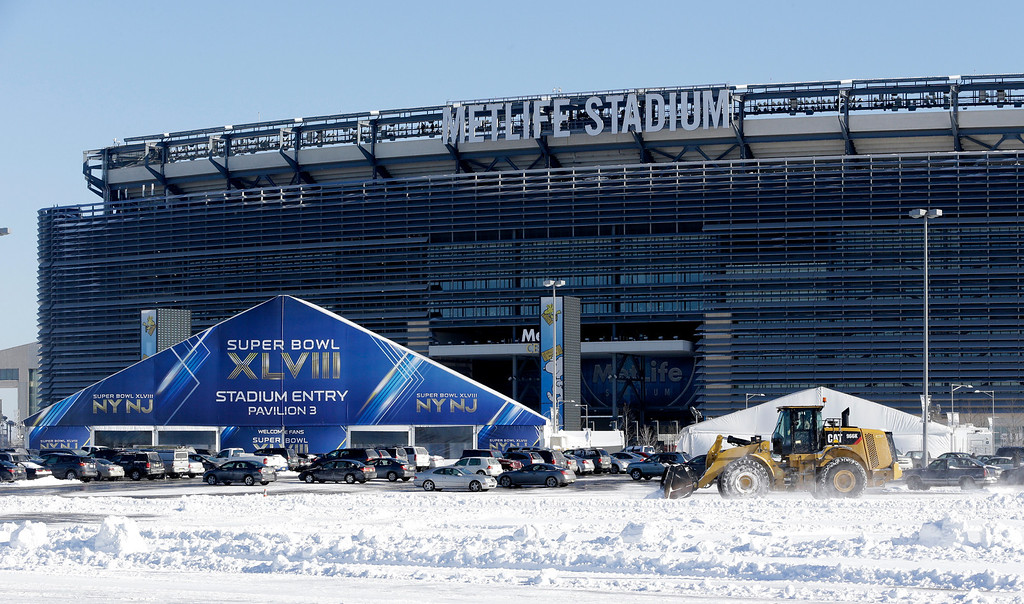 . A tractor plows snow off the parking lot of MetLife Stadium near a tent which will serve as an access point into Super Bowl XLVIII as crews removed snow following a snow storm, Wednesday, Jan. 22, 2014, in East Rutherford, N.J.   (AP Photo/Julio Cortez)