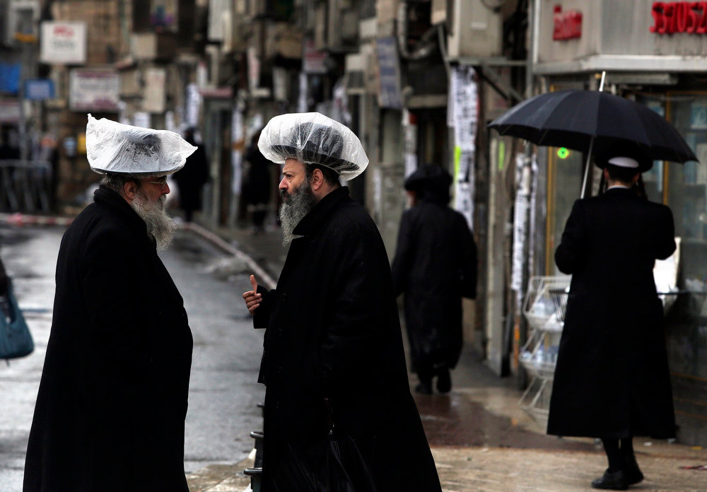 Description of . Ultra-Orthodox Jews, wearing hats covered with plastic against the rain, talk in Jerusalem's Mea Shearim neighbourhood January 8, 2013. Unusually heavy winter rains forced the closure of main access routes to Tel Aviv on Tuesday, causing gridlock in and around Israel's commercial capital, authorities said. The storms were forecast to continue on Wednesday, with rare snowfall expected in Jerusalem. REUTERS/Baz Ratner