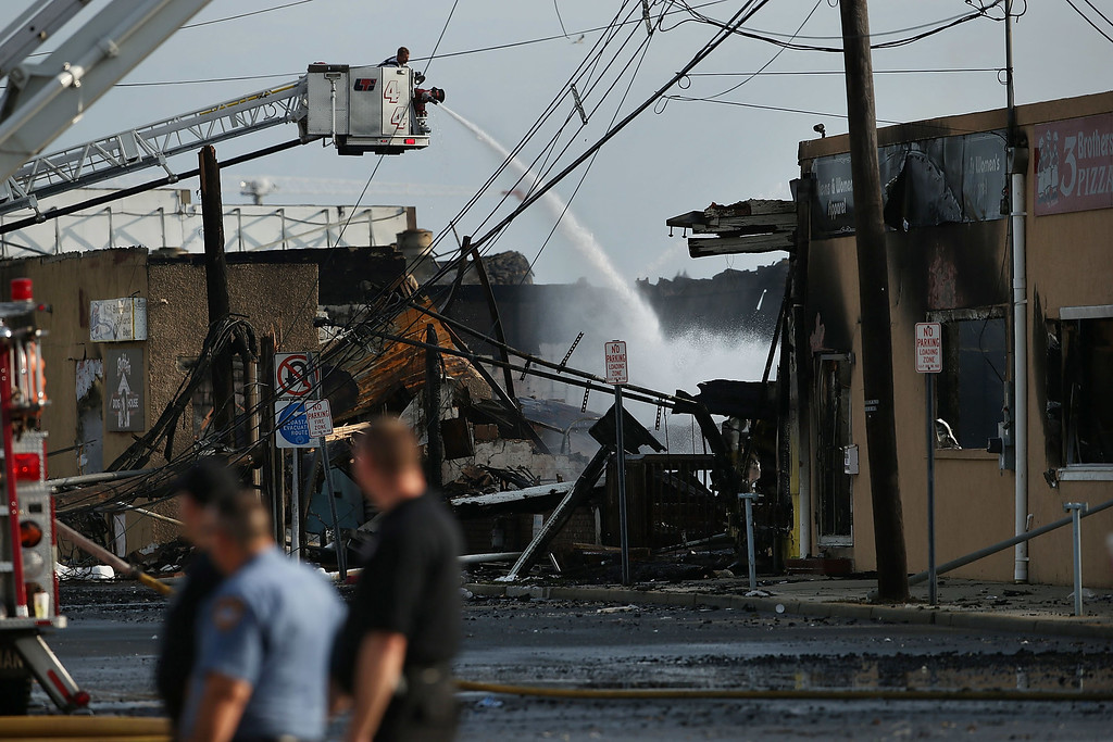 . A firefighter sprays water on a hot-spot at the scene of a massive fire that destroyed dozens of businesses along an iconic Jersey shore boardwalk on September 13, 2013 in Seaside Heights, New Jersey.  (Photo by Spencer Platt/Getty Images)