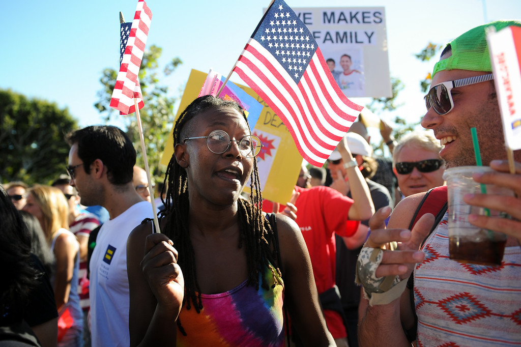 . Pam Noles hands out American flags at the rally in West Hollywood to celebrate the U.S. Supreme Court\'s ruling that killed Prop 8, Wednesday, June 26, 2013. (Michael Owen Baker/L.A. Daily News)
