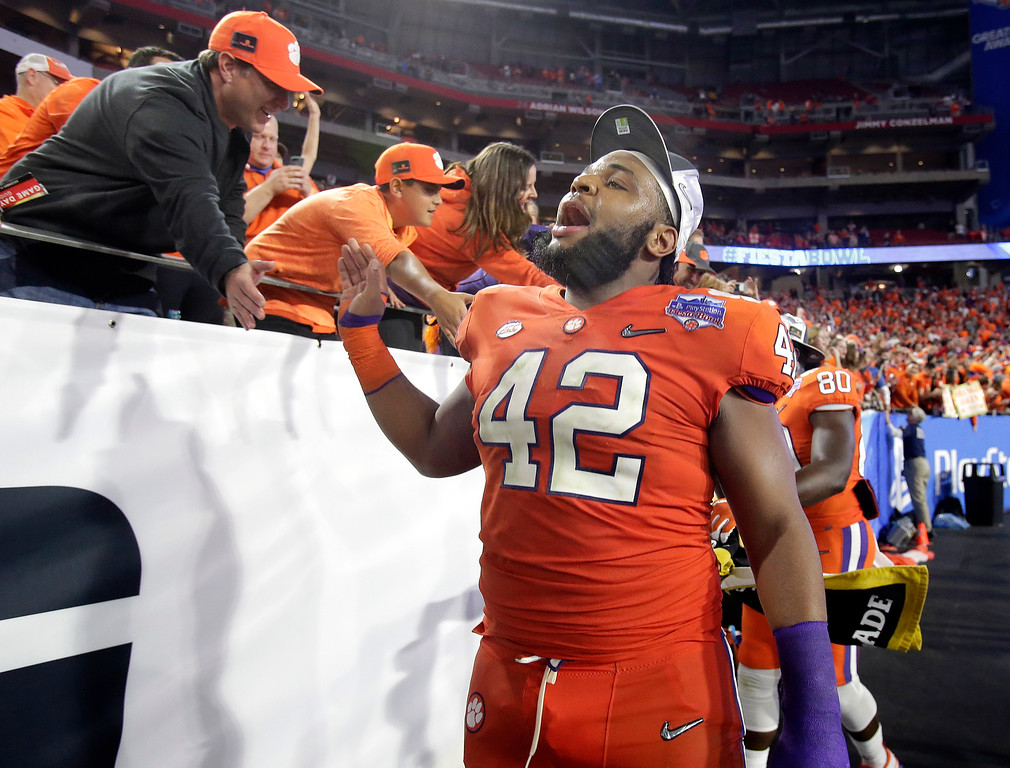 . Clemson defensive lineman Christian Wilkins (42) greets fans after Clemson defeated Ohio State 31-0 in the Fiesta Bowl NCAA college football playoff semifinal, Saturday, Dec. 31, 2016, in Glendale, Ariz. Clemson advanced to the BCS championship game Jan. 9 against Alabama. (AP Photo/Rick Scuteri)