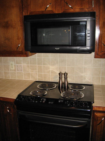 Kitchen appliances, tile countertops and backsplash.