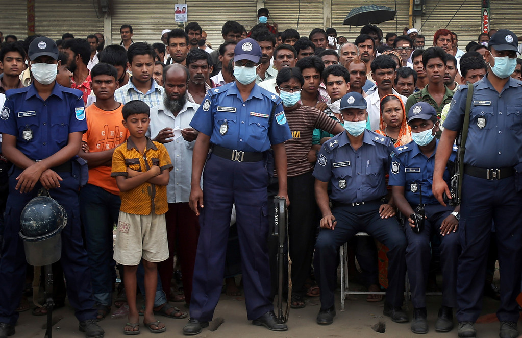 . Policemen stand guard while a crowd gathers to watch workers toiling in a collapsed garment factory building on Tuesday, April 30, 2013 in Savar, near Dhaka, Bangladesh.  (AP Photo/Wong Maye-E)