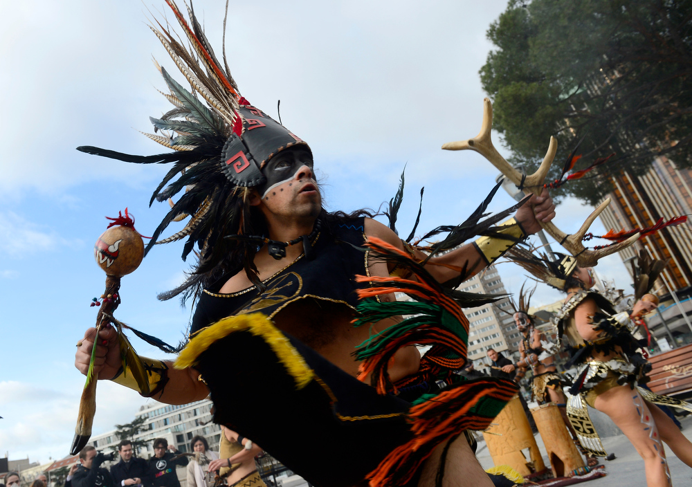 Description of . Dancers dressed in costumes and head-dresses perform during a ceremony marking the end of the Mayan age, on December 21, 2012 in Madrid. Ceremonies are being held to celebrate the end of the Mayan cycle known as Bak'tun 13 and the start of the new Maya Era on December 21.  PIERRE-PHILIPPE MARCOU/AFP/Getty Images