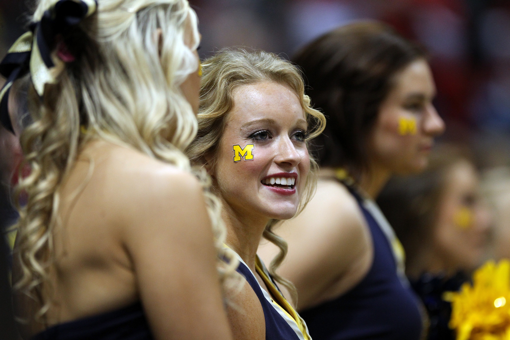 Description of . Michigan Wolverines cheerleaders perform against the Texas Longhorns during the third round of the 2014 NCAA Men's Basketball Tournament at BMO Harris Bradley Center on March 22, 2014 in Milwaukee, Wisconsin.  (Photo by Mike McGinnis/Getty Images)