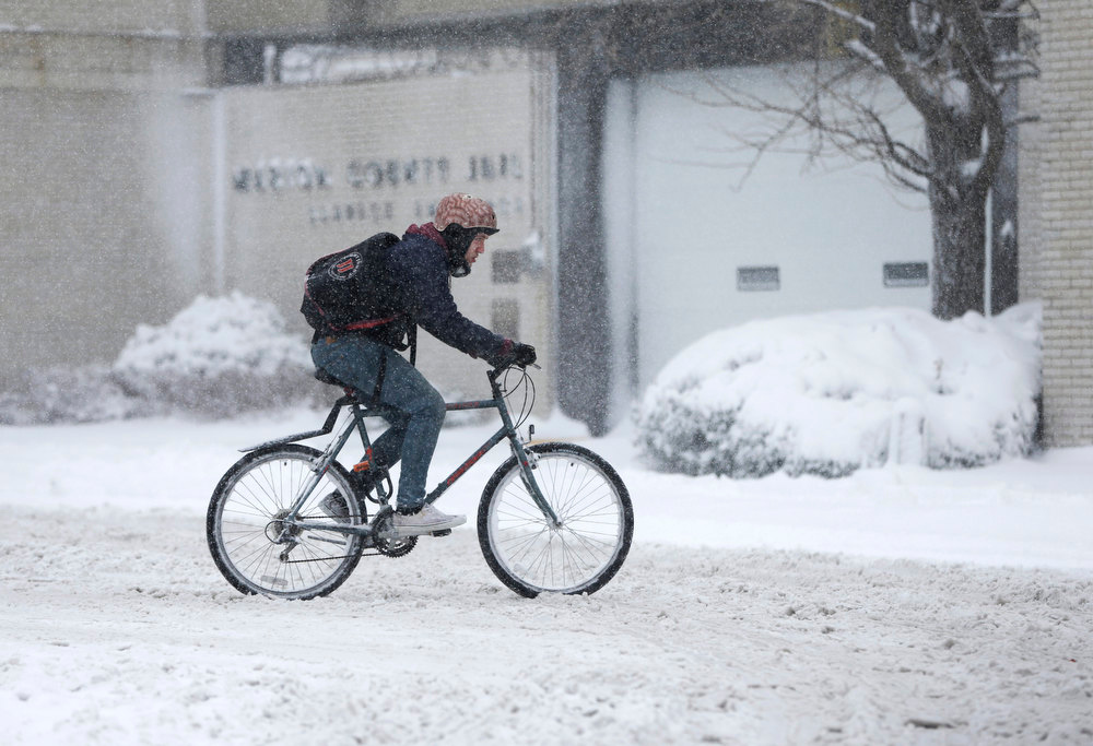 Description of . A delivery man rides his bicycle through the streets as he makes a delivery Wednesday, Dec. 26, 2012, in Indianapolis. The blizzard warning issued the day before by National Weather Service came to fruition in the region Wednesday as winds picked up and snow began falling in earnest before dawn. (AP Photo/Darron Cummings)