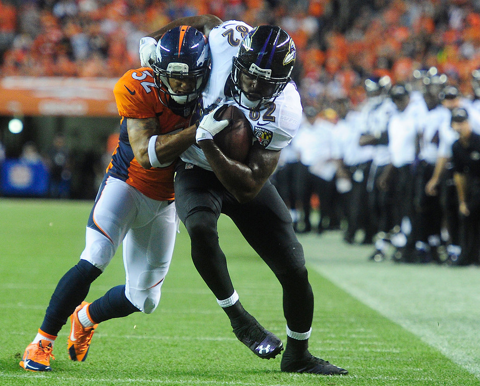 . Denver Broncos defensive back Tony Carter (32) tries to tackle Baltimore Ravens wide receiver Torrey Smith (82) before he makes it to the end zone. (Photo by AAron Ontiveroz/The Denver Post)